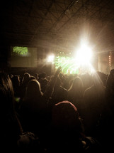 Silhouette of an audience at a worship concert with a spotlight.