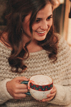 happy woman holding a mug of hot cocoa