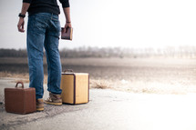 man standing next to a suitcase holding a Bible and looking down a road wondering where to go from here