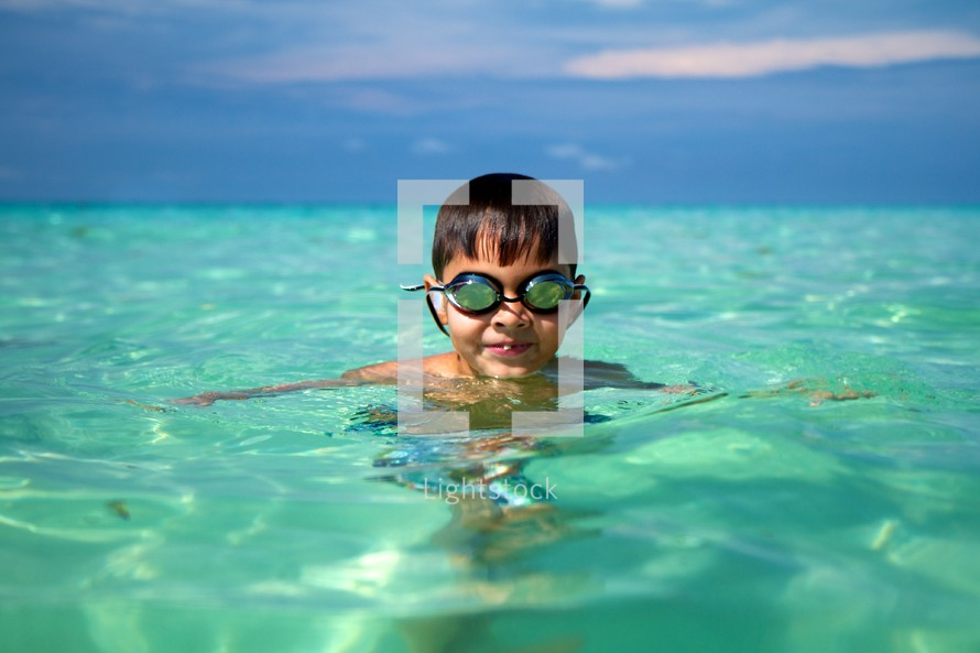 A young boy wearing goggles in the ocean