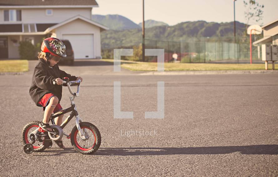 boy child riding a bike with a helmet and training wheels