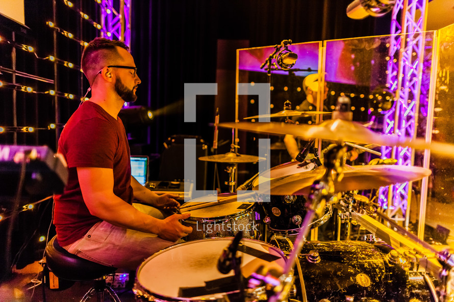 A drummer in a sound studio on stage live worshipping  eyes closed
