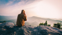 man sitting at the top of a mountain looking out at the view