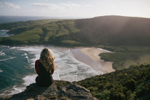 a woman sitting on a cliff looking out at the ocean below