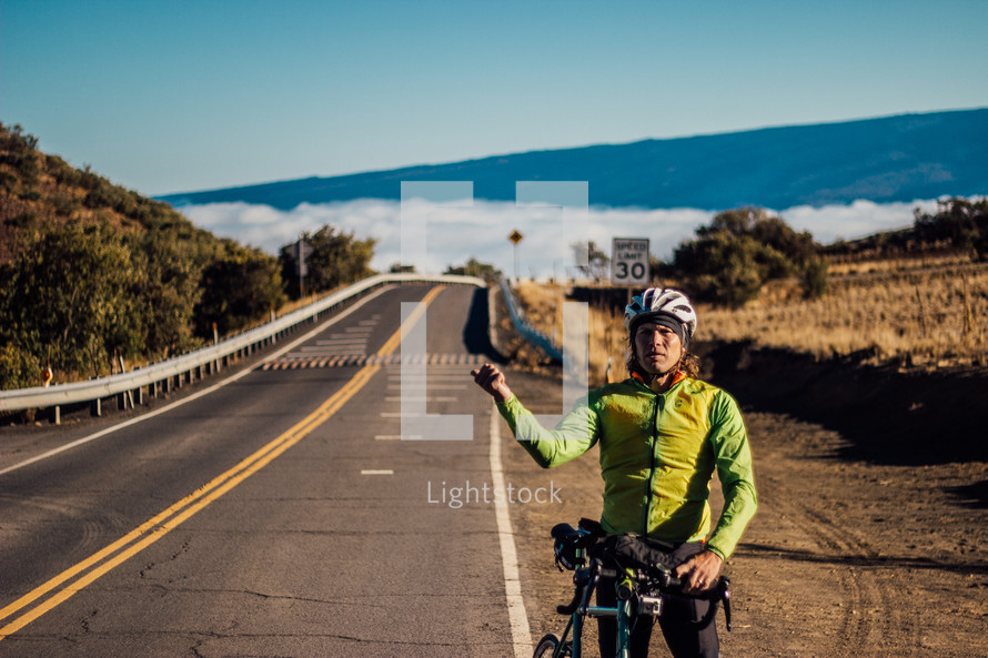 a man with a bike with thumbs out on the side of a road