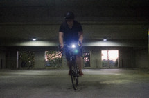 man riding a bicycle in a parking garage