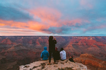 people sitting at the edge of a cliff overlooking a canyon at sunset