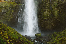 waterfall off the side of a cliff and moss covered rocks