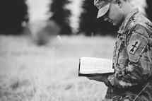 serviceman kneeling in prayer in a field reading a Bible