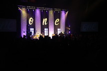 The word one on a stage at a contemporary worship service.