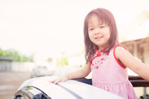 Little girl in the car looking out a sunroof.