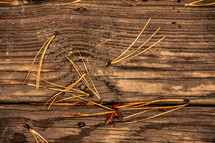 pine straw on a wood deck