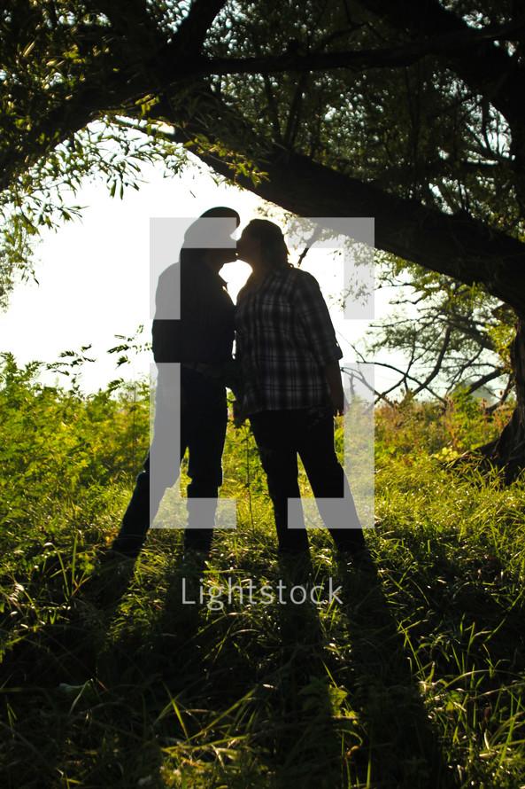 man in a cowboy hat kissing a woman