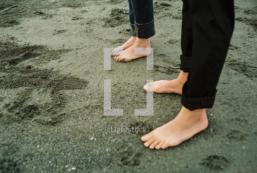 Barefoot couple in sand