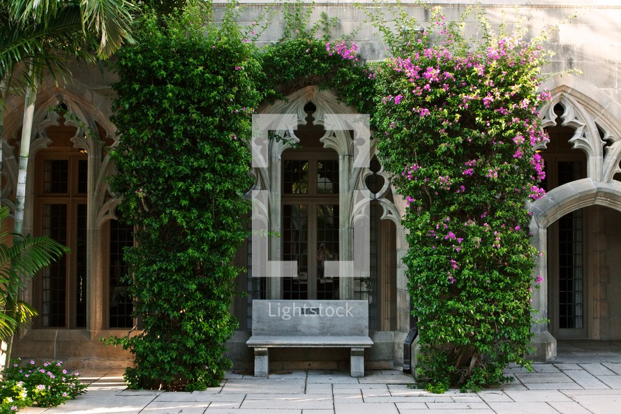 flowers and ivy growing over an archway to a church