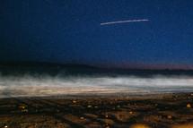 streak in the sky above a beach