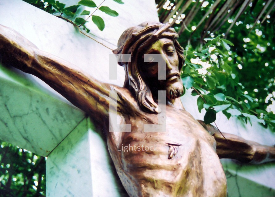 A bronze sculpture of Jesus on the cross showing where he was pierced with a spear and hung on the cross to die for the sins of mankind. Jesus is shown here on a marble cross and a bronze statue depicting Jesus wearing a crown of thorns and nails in his feet and hands.