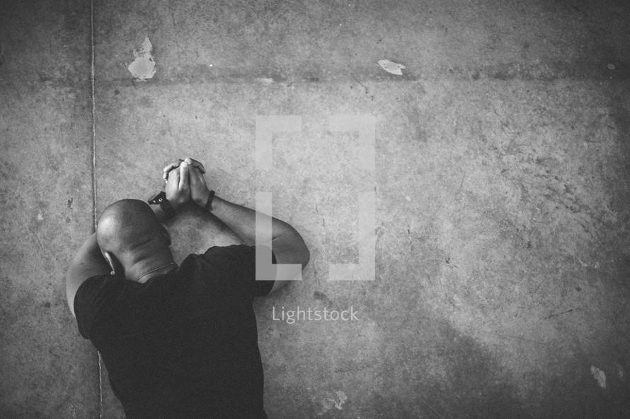 Man lying face down on floor in prayer.
