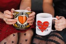 women holding coffee mugs with hearts