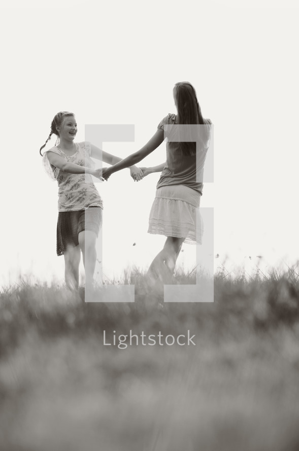 Girls holding hands playing in a field