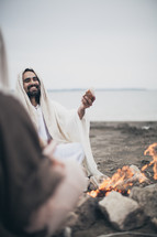 Jesus breaking bread with his disciples around a campfire on the beach.