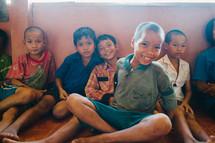 smiling boys sitting against a wall