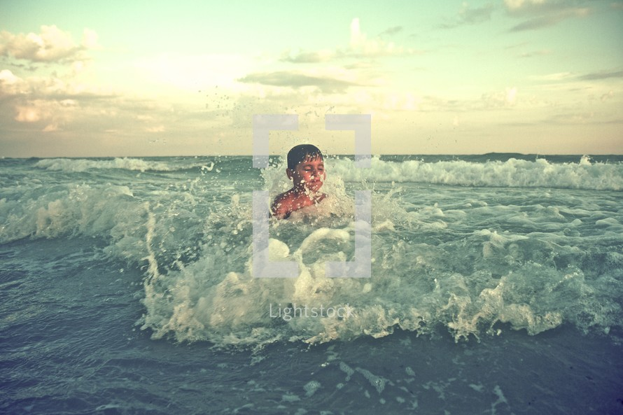 A boy splashing in the waves of the ocean