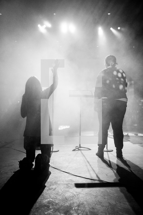 A back view of two people singing and worshiping on stage