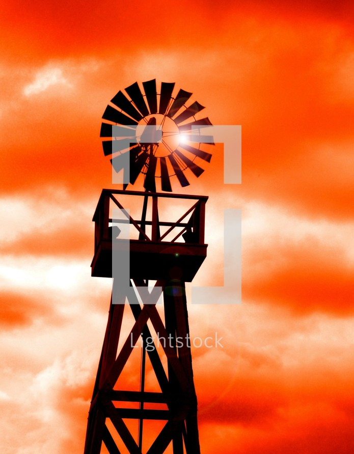 A Windmill silhouetted against an orange sunset  used to harness the power of the wind on a rural farm.