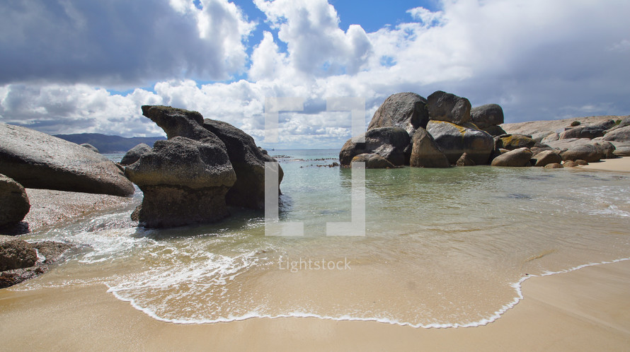 Large boulders on sandy beach with cloudscape behind