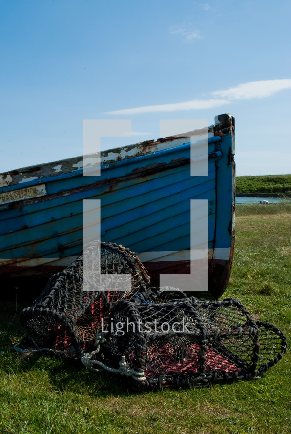 old boat and crab cages on the shore