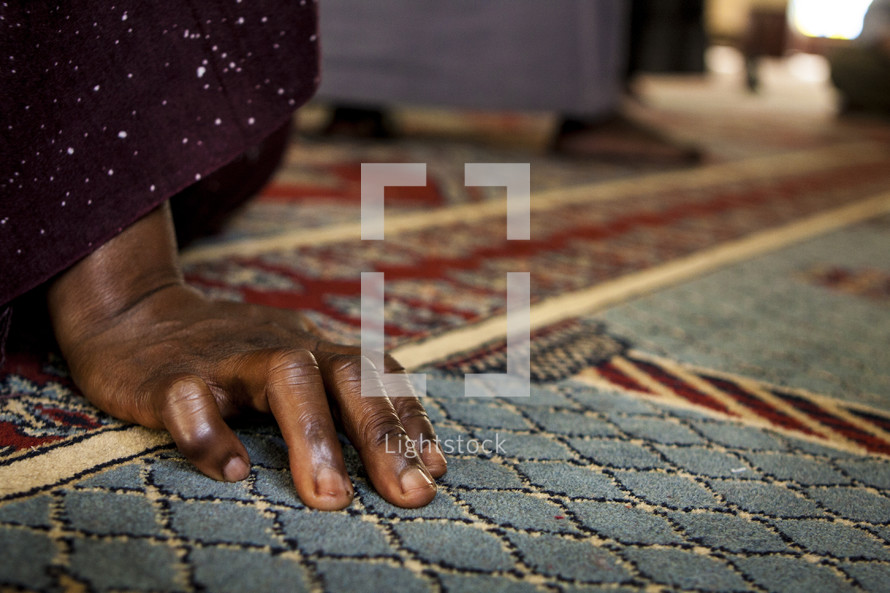 A Ugandan's hand rests on the floor