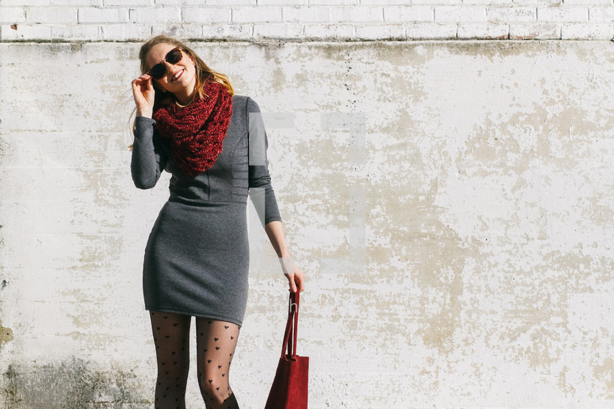 red purse, purse, bag, panty hose, sunglasses, scarf, shades, outdoors, smiling, woman