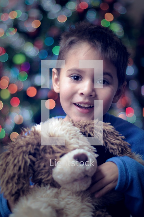 Little boy snuggling a stuffed animal  in front of a Christmas tree