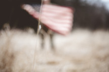 out of focus soldier in a field holding an American flag