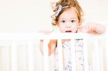 a toddler girl in a crib