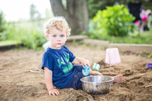 toddler boy playing in a sand box