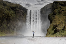 a person standing in front of a waterfall with hands raised