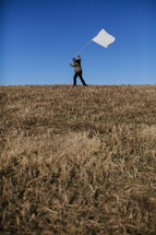 Man carrying white flag on grassy hilltop.