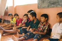 boys sitting against a wall