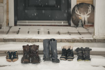 boots on porch steps covered in snow