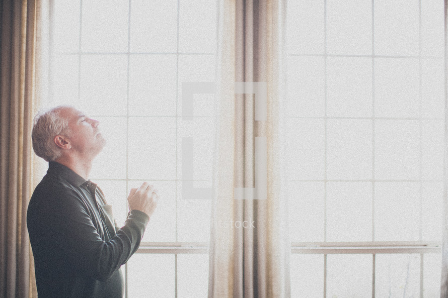elderly man standing at a window praying to God