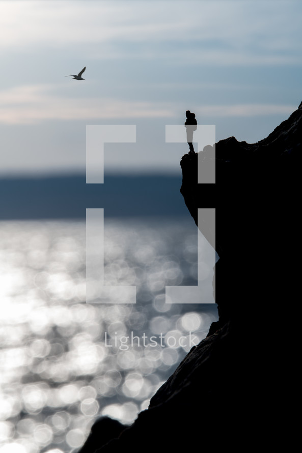 silhouette of a person standing at the edge of a cliff over the ocean