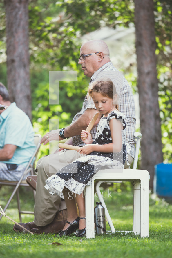 a grandfather sitting outdoors with his granddaughter