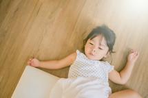 tired toddler girl asleep on the floor