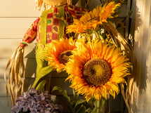 sunflowers and scarecrow on a porch in fall