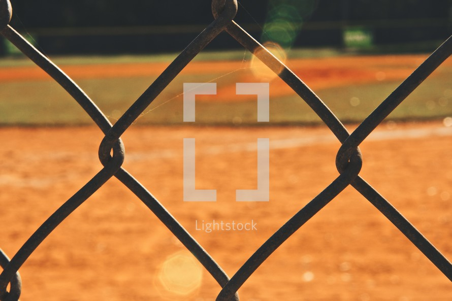 baseball field through a chain linked fence
