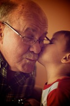 A boy kissing his grandfather on the cheek