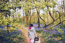 a girl walking on a path in the woods carrying a picnic basket