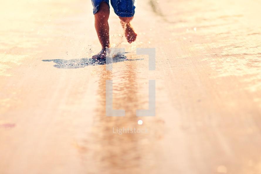A young boy runs through water and makes a splash